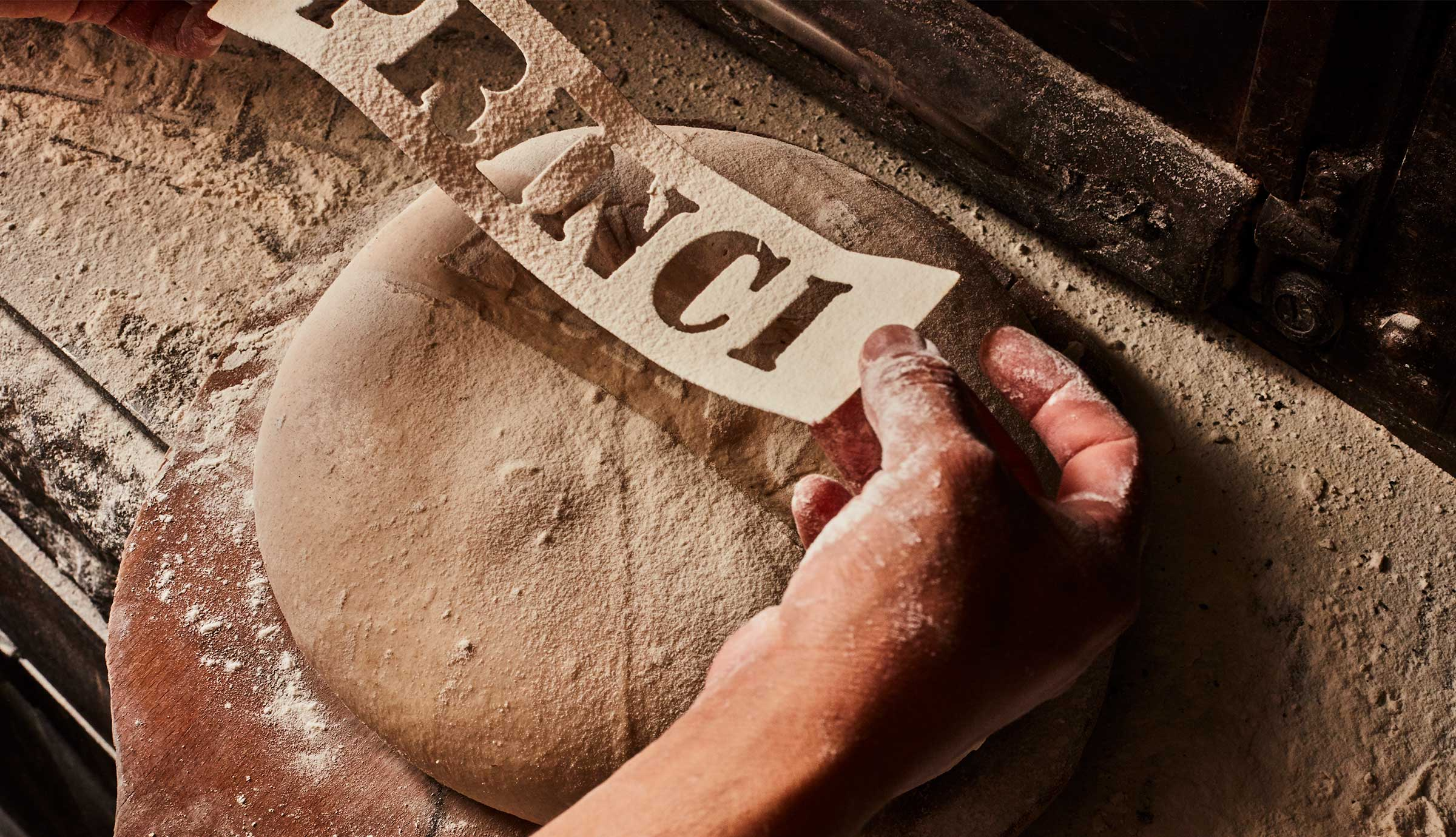 A stencil that reads Princi is held over bread dough