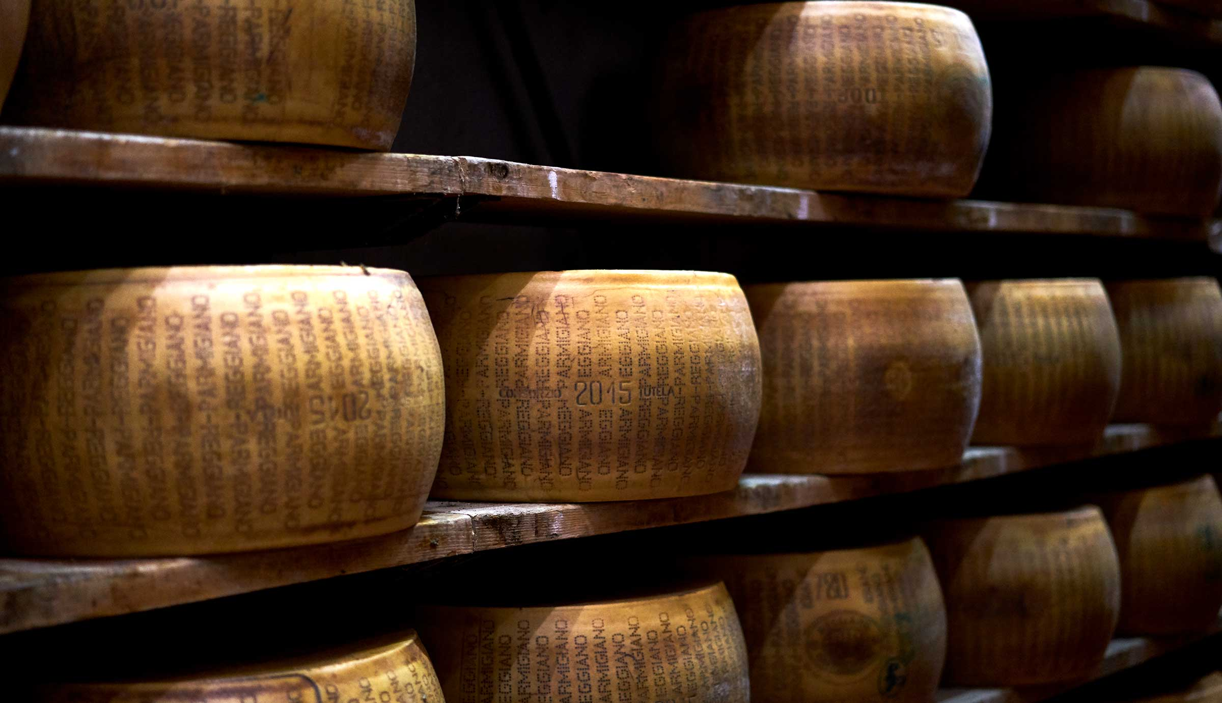 Wheels of Parmigiano Reggiano cheese stacked on shelves